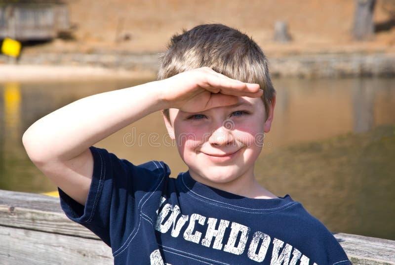 Giovane ragazzo che protegge i suoi occhi fotografia stock