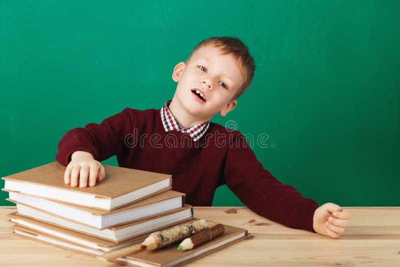 Giovane ragazzo che sembra arrabbiato scuotendo i suoi pugni stanchi della lezione della scuola fotografia stock libera da diritti
