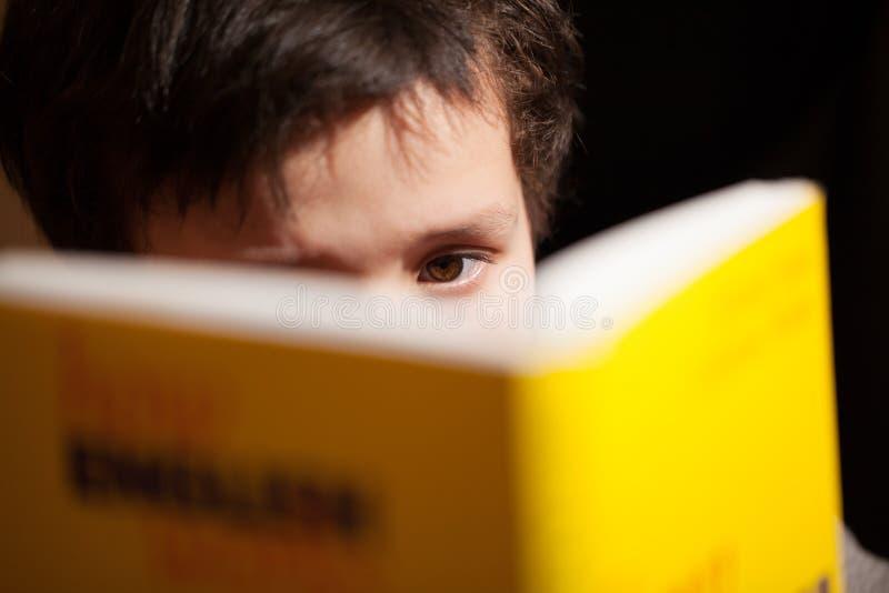 Giovane ragazzo che si concentra sulla lettura del libro fotografia stock libera da diritti