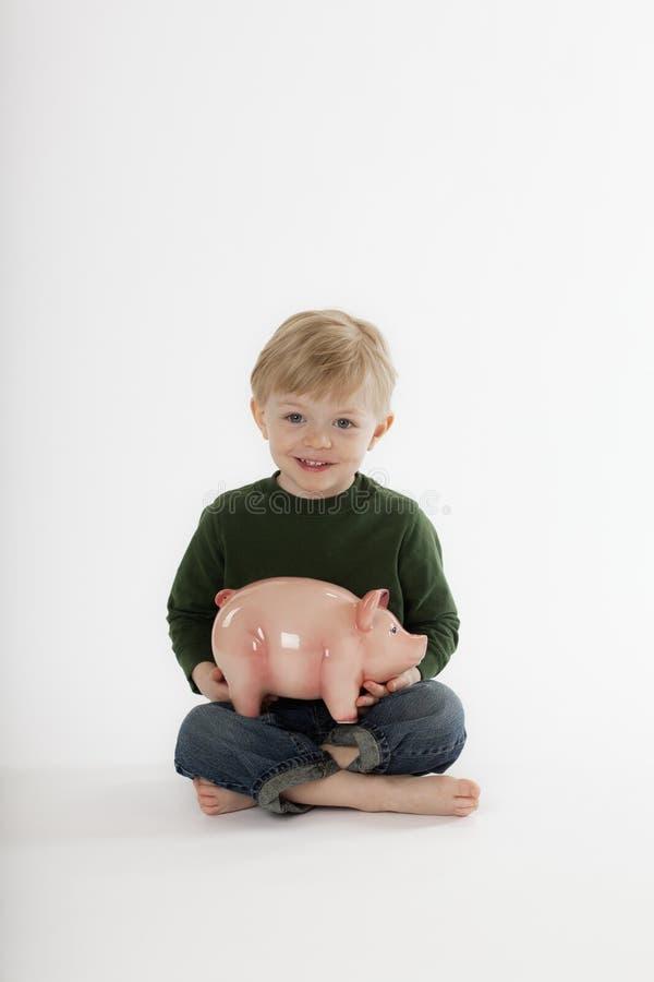Giovane ragazzo che si siede con la Banca Piggy immagine stock
