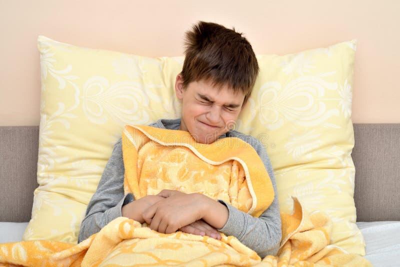 Giovane ragazzo che si siede a letto con il mal di stomaco fotografia stock libera da diritti