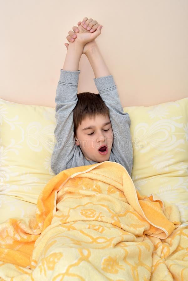 Giovane ragazzo che si siede a letto sbadiglio ed allungamento fotografia stock