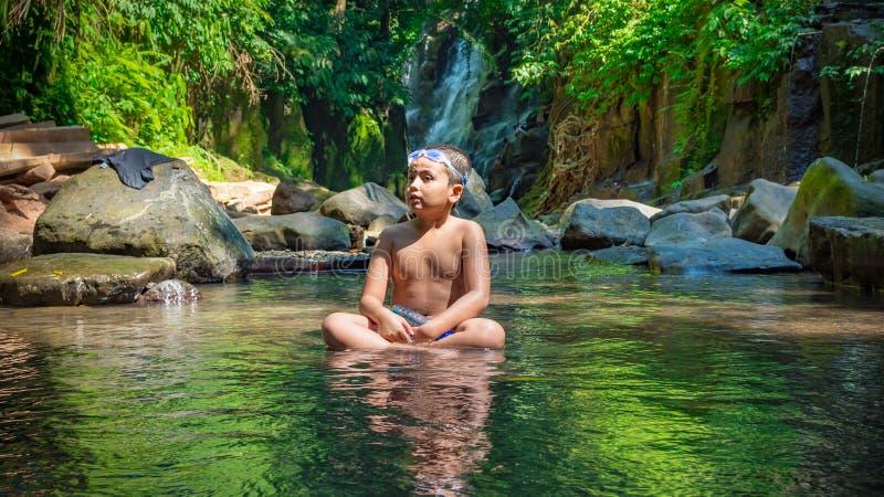 Giovane ragazzo che si siede in una corrente che gode della foresta pluviale del amd dell'acqua intorno lui fotografie stock libere da diritti