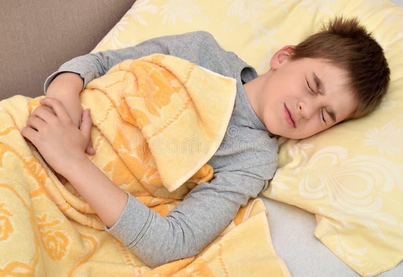 Giovane ragazzo che si trova a letto con il mal di stomaco fotografia stock libera da diritti