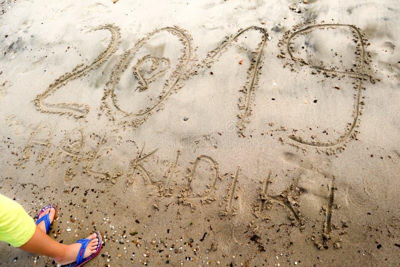 Giovane ragazzo che sta davanti al numero 2019 scritto sulla sabbia di mare con cuore tirato di numero 0 e testo Halkidiki fotografie stock