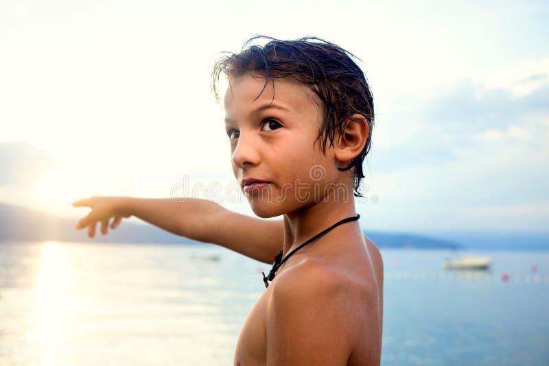 Giovane ragazzo che sta indicante nel cielo davanti al mare fotografie stock libere da diritti