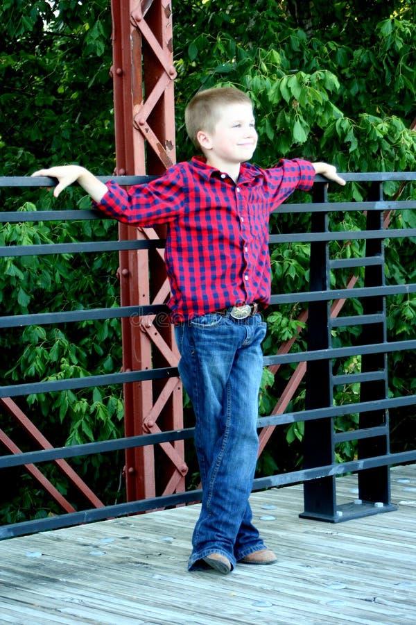 Giovane ragazzo che sta su un ponte fotografia stock