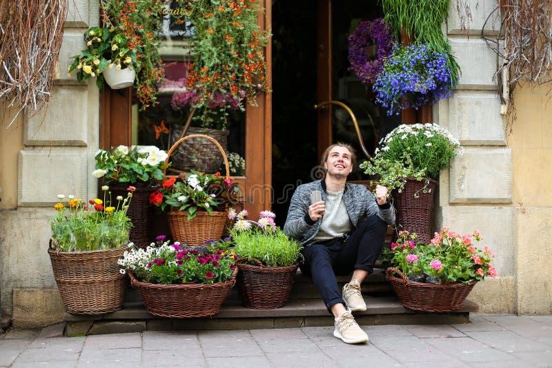 Giovane ragazzo che tiene gli smartphone e siede in un negozio di fiori vicino ai bouquet nei cestini fotografia stock
