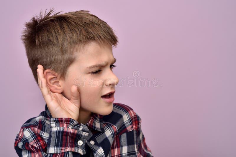 Giovane ragazzo che tiene la sua mano sull'orecchio-ascoltare di nascosto fotografia stock