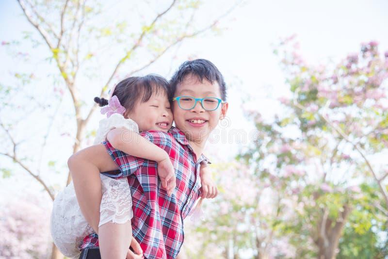 Giovane ragazzo che tiene la sua parte posteriore della sorella sopra fotografie stock libere da diritti
