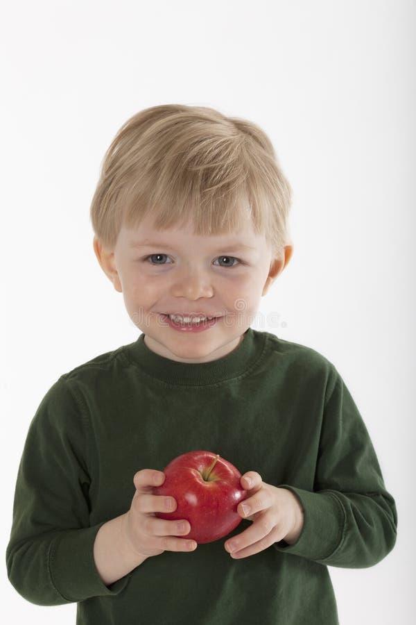 Giovane ragazzo che tiene un Apple fotografia stock libera da diritti
