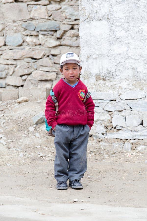 Giovane ragazzo che va a casa dalla scuola dopo le lezioni alla scuola locale a Lamayuru Gompa, Ladakh, India del nord fotografia stock
