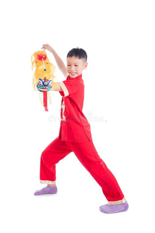 Giovane ragazzo cinese che gioca il burattino cinese del leone fotografie stock