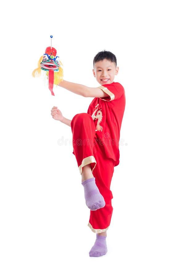Giovane ragazzo cinese che gioca il burattino cinese del leone immagini stock libere da diritti