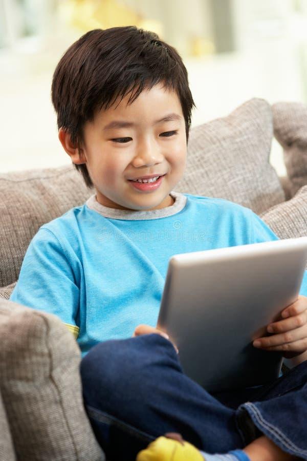 Giovane ragazzo cinese che per mezzo del calcolatore del ridurre in pani immagini stock