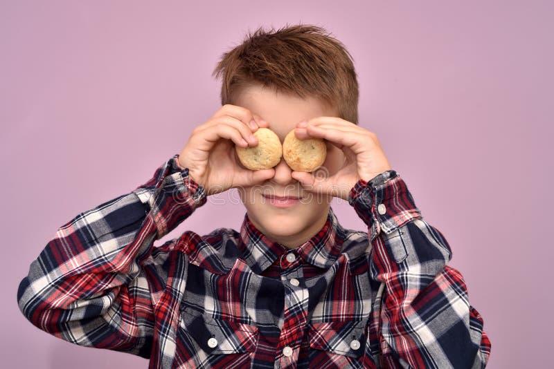 Giovane ragazzo con i biscotti invece degli occhi fotografie stock libere da diritti