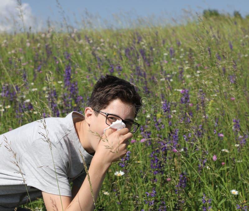 Giovane ragazzo con i vetri nei prati con l'allergia fotografia stock libera da diritti