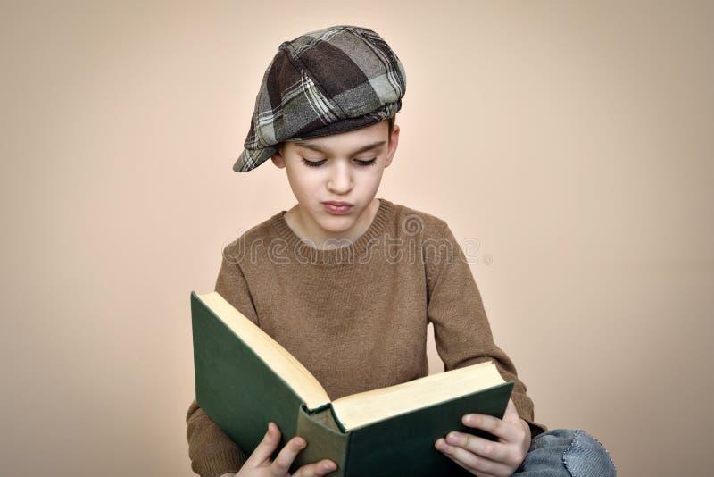 Giovane ragazzo con il cappuccio che legge un vecchio libro immagini stock