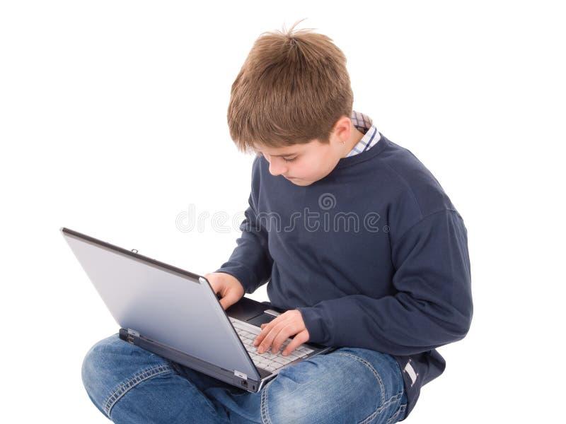 Giovane ragazzo con il computer portatile fotografie stock libere da diritti