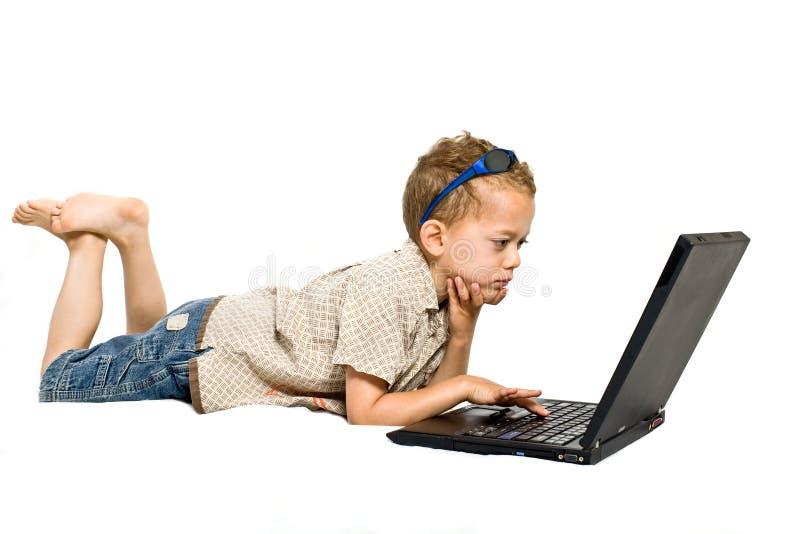 Giovane ragazzo con il computer portatile immagine stock