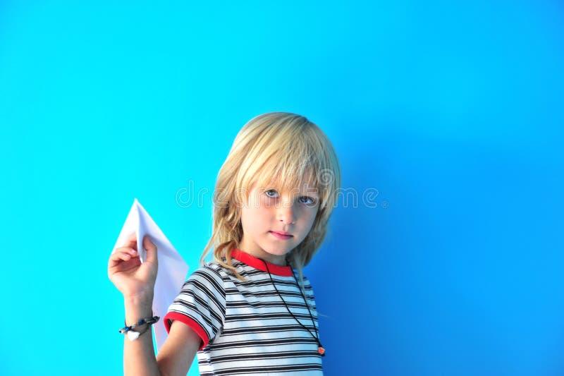 Giovane ragazzo con l'aereo di carta immagine stock