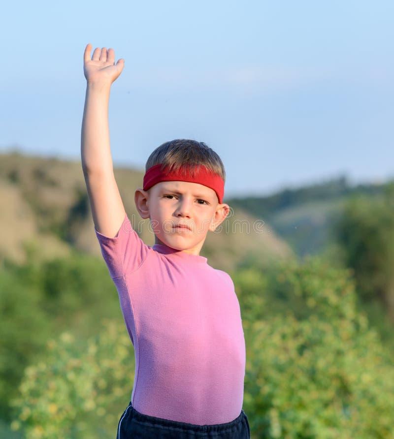 Giovane ragazzo con la fascia che alza il suo un braccio fotografia stock