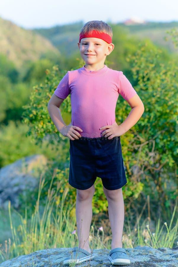 Giovane ragazzo con la fascia che alza il suo un braccio immagine stock