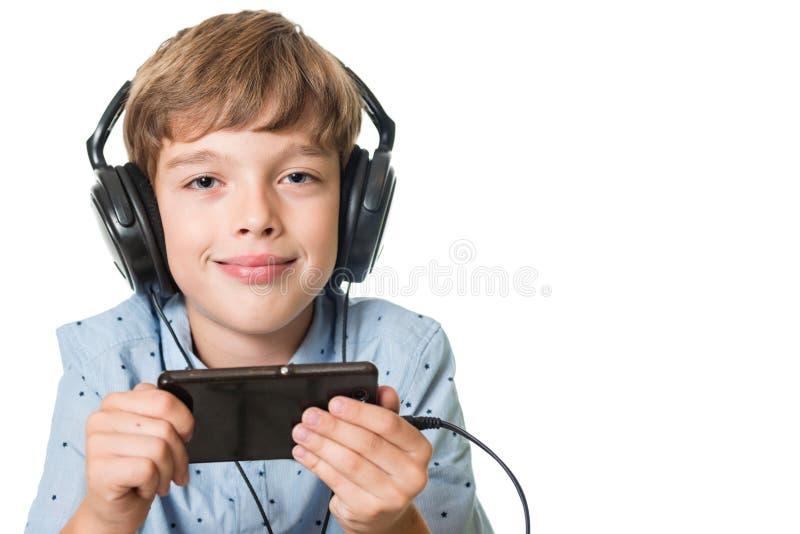 Giovane ragazzo con le cuffie che ascolta la musica fotografia stock