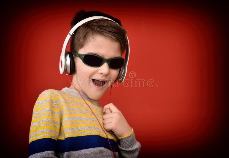 Giovane ragazzo con le cuffie che gode della musica fotografie stock