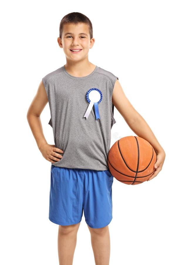 Giovane ragazzo con un distintivo e una pallacanestro del vincitore immagine stock libera da diritti