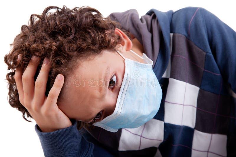 Giovane ragazzo con una mascherina medica e mano sulla testa fotografia stock