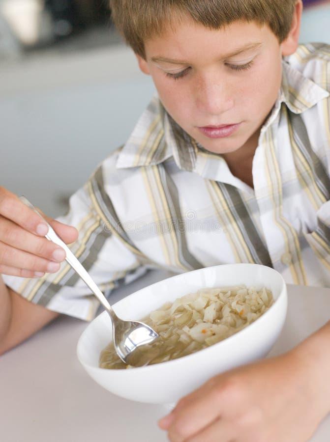 Giovane ragazzo in cucina che mangia minestra fotografia stock libera da diritti