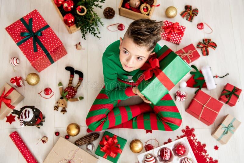 Giovane ragazzo curioso che porta i pigiami di natale che si siedono sul pavimento sul giorno di Natale, scuotente il suo regalo  immagini stock