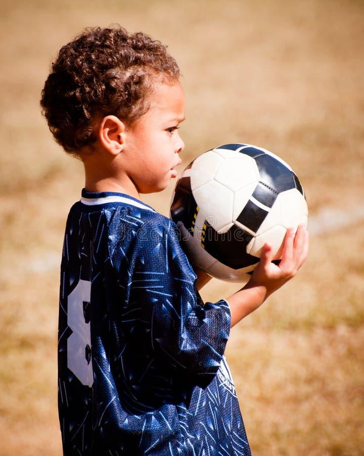Giovane ragazzo del African-American con la sfera di calcio fotografie stock