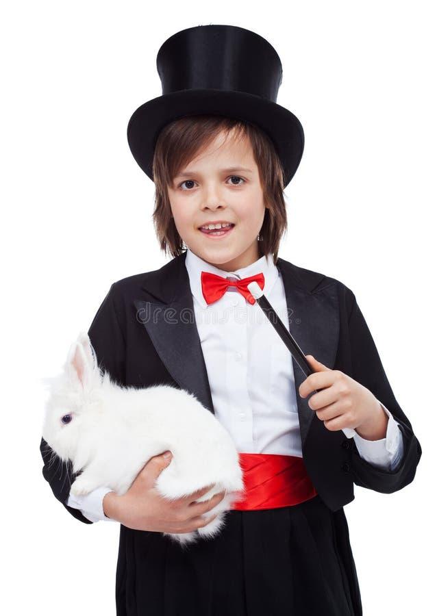 Giovane ragazzo del mago che tiene coniglio bianco fotografia stock libera da diritti