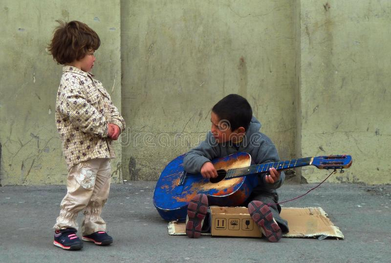 Giovane ragazzo del musicista della via che gioca la sua chitarra blu mentre ragazza che ascolta e che gode immagine stock libera da diritti