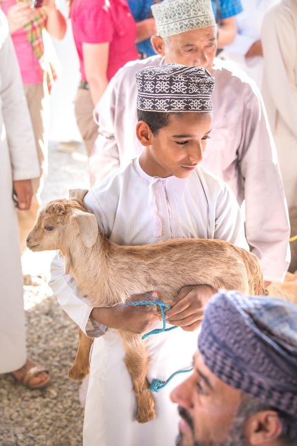 Giovane ragazzo dell'Oman che tiene una capra del bambino fotografie stock