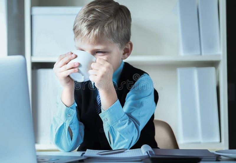 Giovane ragazzo di affari che lavora al computer portatile che tiene tazza di caff? bianca o t? caldo Piccolo capo divertente in  fotografie stock libere da diritti