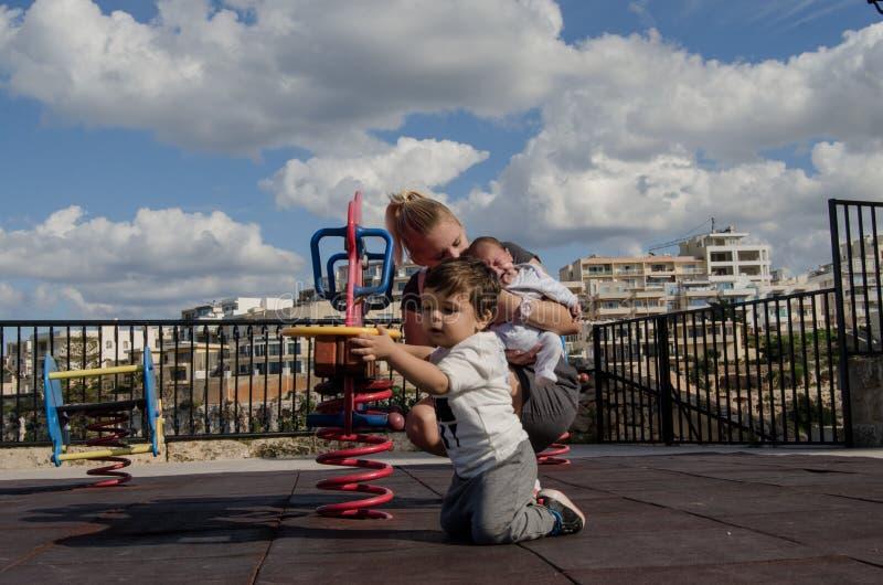 Giovane ragazzo di neonato biondo della tenuta della madre e giocare con il bambino nel parco del bambino fotografie stock
