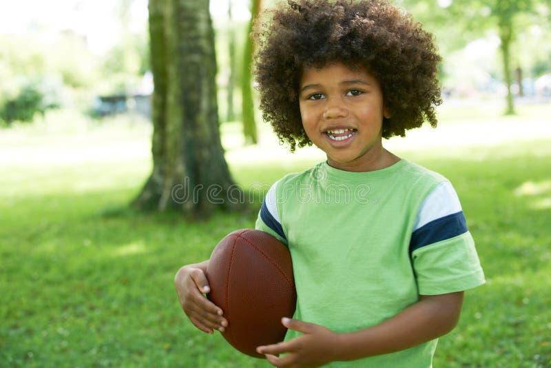 Giovane ragazzo felice che gioca nel parco con football americano immagine stock libera da diritti
