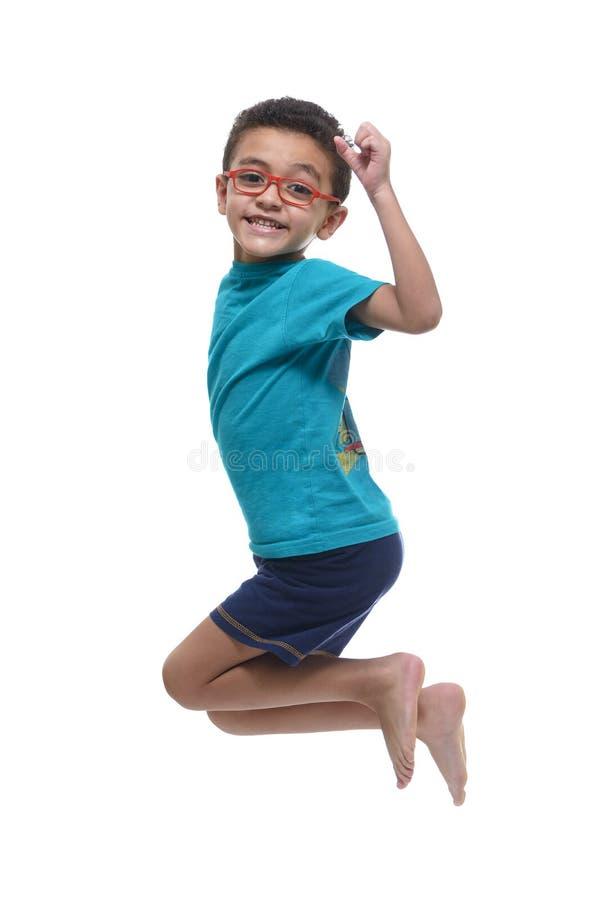 Giovane ragazzo felice che salta nell'aria fotografia stock