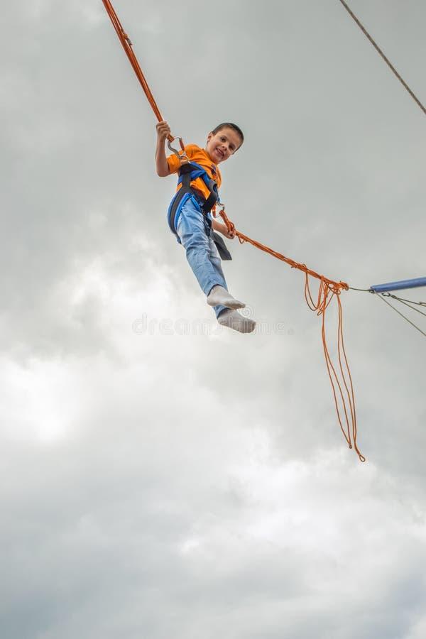 Giovane ragazzo felice che salta sul trampolino dell'ammortizzatore ausiliario fotografie stock