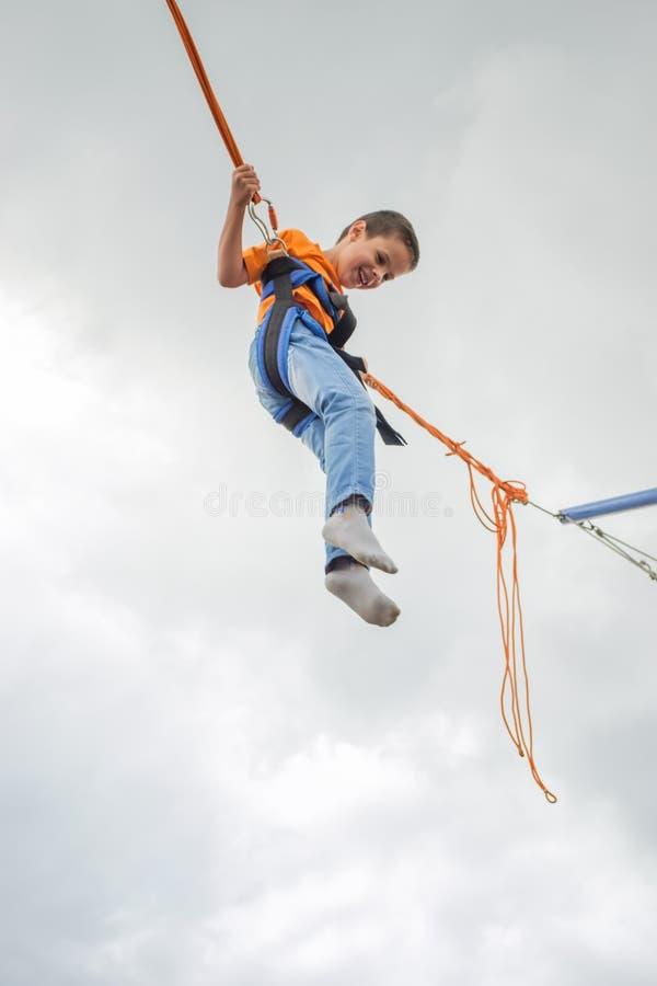 Giovane ragazzo felice che salta sul trampolino dell'ammortizzatore ausiliario fotografia stock