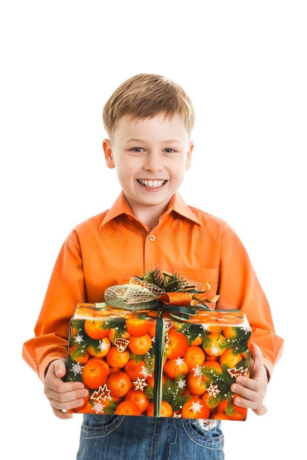 Giovane ragazzo felice con i sorrisi attuali di una scatola isolato immagini stock libere da diritti