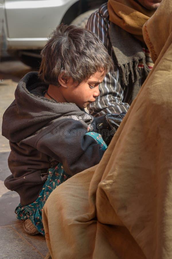 Giovane ragazzo indiano dalla famiglia povera sulla via a Jaipur Il Ragiastan L'India fotografie stock libere da diritti