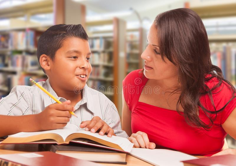 Giovane ragazzo ispano ed adulto di Famle che studia alla biblioteca immagini stock libere da diritti