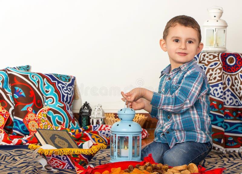 Giovane ragazzo musulmano felice che gioca con la lanterna del Ramadan - aspetti per fotografia stock libera da diritti