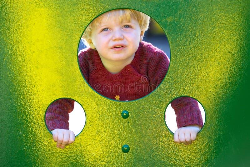 Giovane ragazzo o bambino che osserva attraverso i fori in una parete in un campo da giuoco fotografia stock