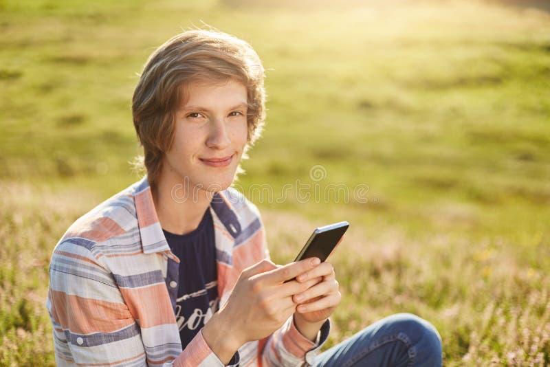 Giovane ragazzo piacevole con gli occhi scuri dello stretto ed i capelli alla moda che si siedono al telefono cellulare della ten immagine stock libera da diritti