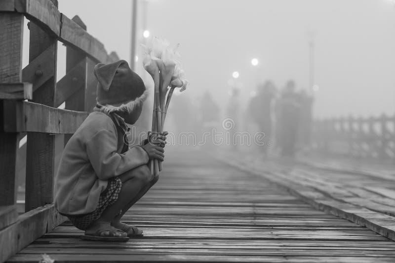 Giovane ragazzo povero solo che vende i fiori al ponte di legno di lunedì nella mattina fredda immagine stock